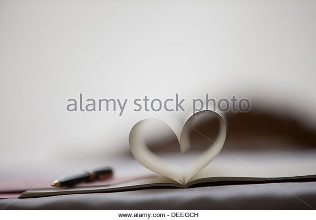 Pen and pages of notebook forming heart-shape - Stock-Bilder