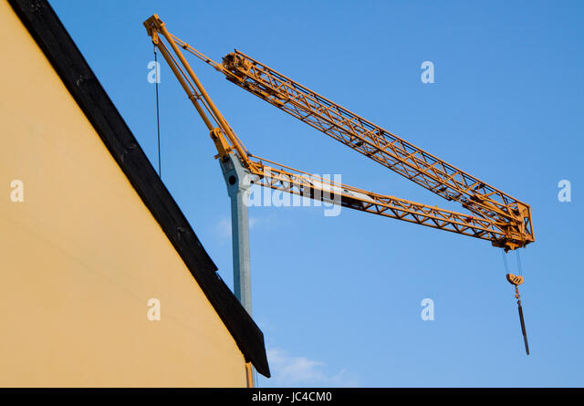A construction crane against a blue sky and a yellow Suffolk cottage - Stock Image