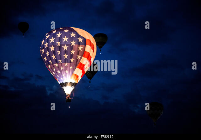 Illuminated Stars and Stripes hot air balloon flying Dawn Patrol, Albuquerque International Balloon Fiesta, New - Stock-Bilder