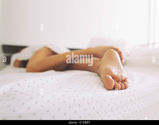 Feet of a woman sleeping in bed at home. Legs of a female lying on bed - Indoors - Stock Image