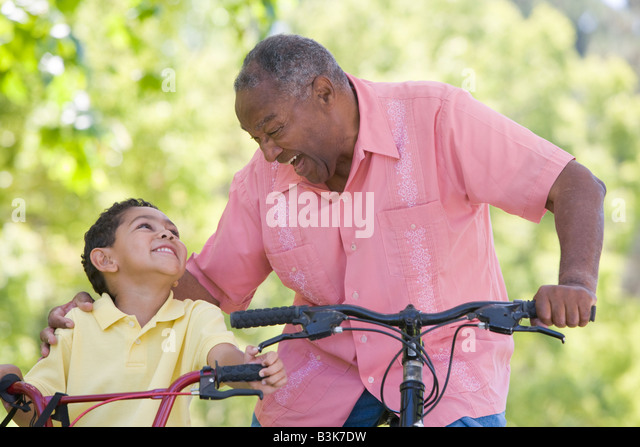 Grandfather and grandson on bikes outdoors smiling - Stock-Bilder