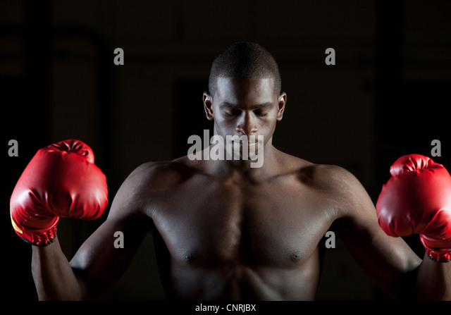Boxer in boxing gloves with eyes closed, portrait - Stock Image