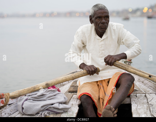 Boatman rowing on the Ganges River - Varanasi, India - Stock Image