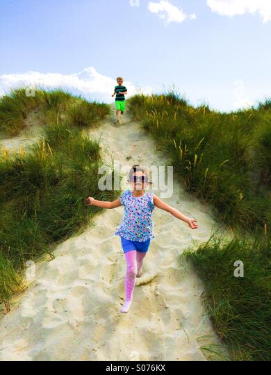 Two five year old children playing in sand dunes - Stock Image
