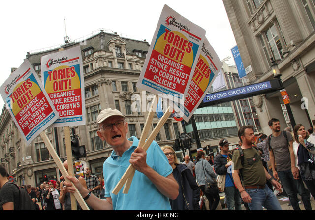 London, UK - 1 July 2017 - A demonstrator holds up placards by Oxford Street station ahead of the Tories Out march - Stock Image