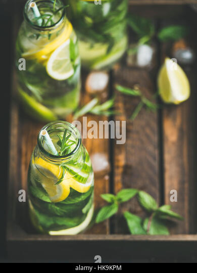Citrus fruit and herbs infused sassi water for detox, healthy eating, dieting in glass bottles in wooden tray, selective - Stock Image