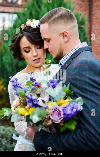 Portrait of emotional newlyweds groom and bride embracing  holding each other hands. In yard against house in autumn - Stock Image