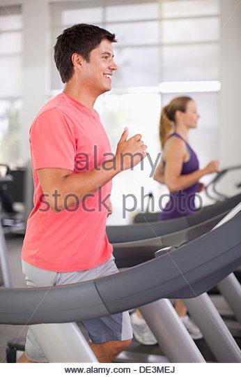 Smiling man running on treadmill in gymnasium - Stock-Bilder