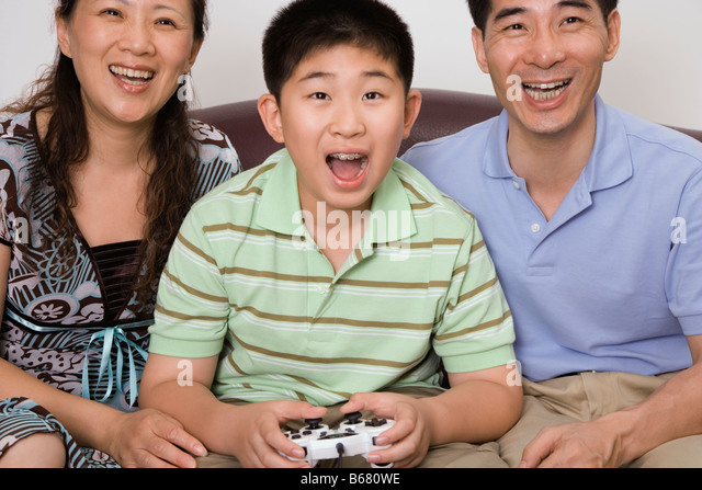 Mature couple sitting with their son playing video game - Stock Image