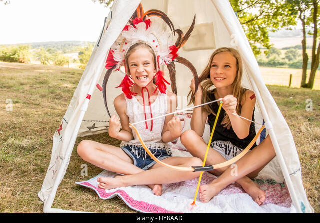 Young twins sit in a wigwam outside in the sunshine - Stock Image