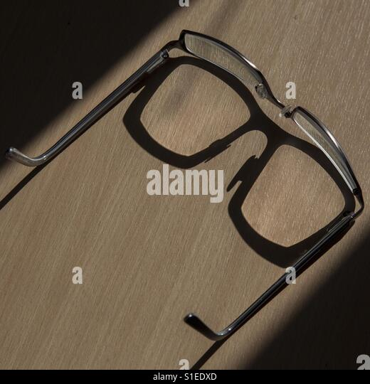 Shadow cast by spectacles on desk - Stock Image