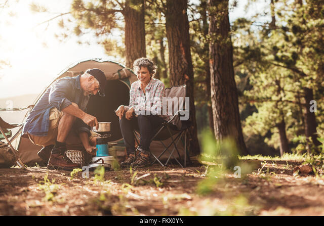 Happy campers outdoors in the wilderness and making coffee on a stove. Senior couple on a camping holiday. - Stock Image