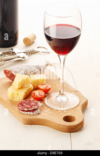 Red wine and assortment of cheese and snacks on white background - Stock-Bilder