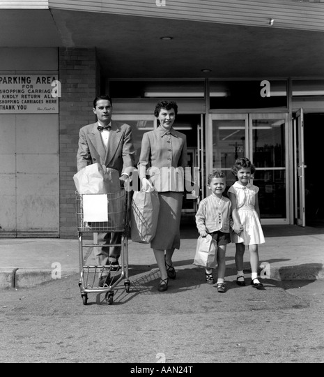1950s FAMILY MAN WOMAN GIRL BOY WALKING OUT OF SUPERMARKET STORE MOTHER AND SON CARRYING BAGS FATHER PUSHING GROCERY - Stock-Bilder