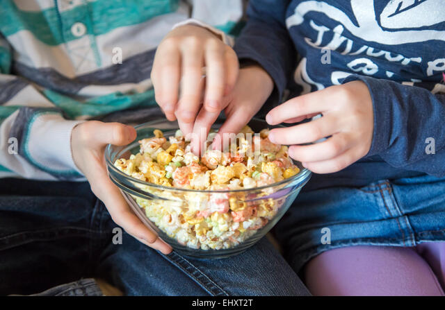 Hands of boy and girl taking coloured popcorn - Stock Image