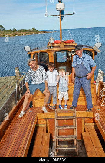 Father and two sons with fisherman on boat, Eggergrund, Sweden - Stock Image