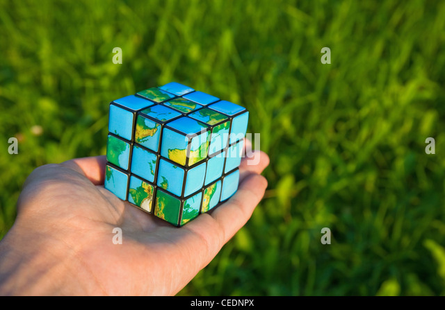 Cube in the manner of planets land on palm on background of the herb - Stock Image