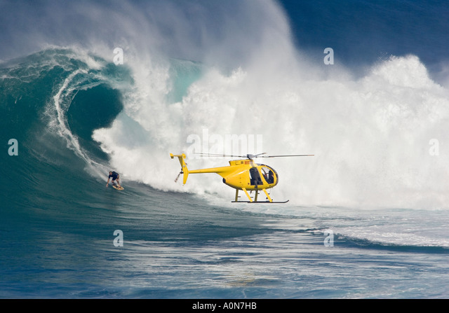 A helicopter filming tow in surfer, Laird Hamilton at Peahi, (Jaws) off Maui, Hawaii. - Stock-Bilder