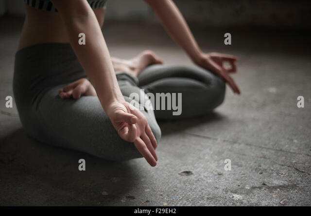 Woman practicing lotus pose in yoga studio, Munich, Bavaria, Germany - Stock Image