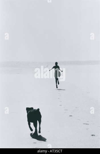 A woman and dog running on the beach - Stock Image