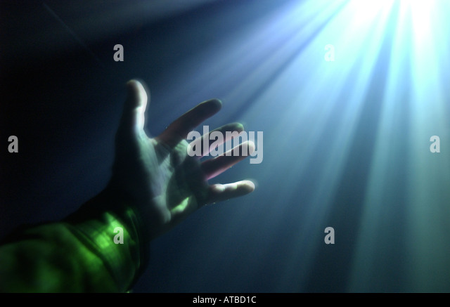 hand reaching out in a ray of light, photo by Bruce Miller - Stock Image