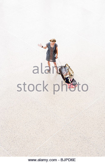 A woman looking at clothes falling out of her suitcase - Stock Image