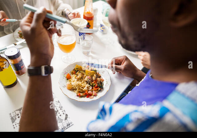 Cropped image of friends eating food at table - Stock-Bilder