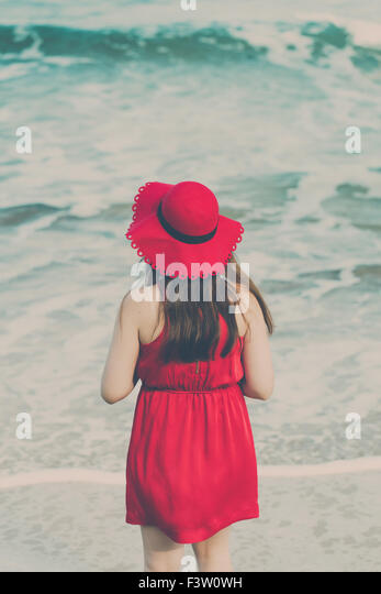 Young woman in a red dress on the beach - Stock Image