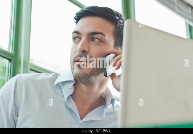 Close up of young male office worker talking on mobile phone - Stock-Bilder