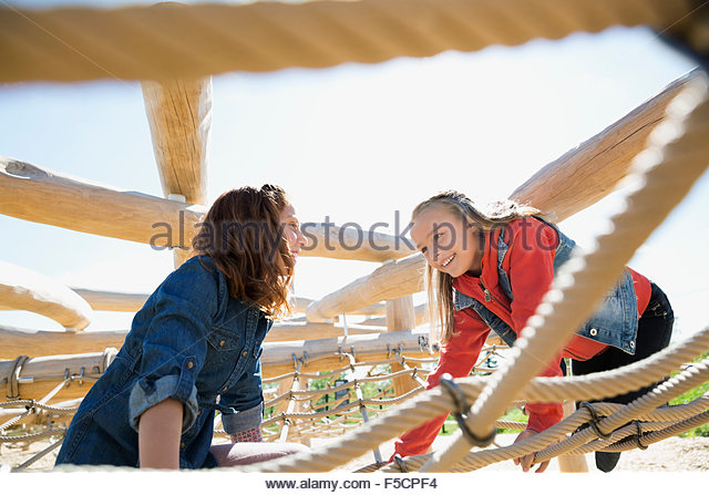 Girls climbing playing on net at sunny playground - Stock Image