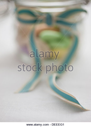 Close up of pastel candies in jar with ribbon - Stock Image