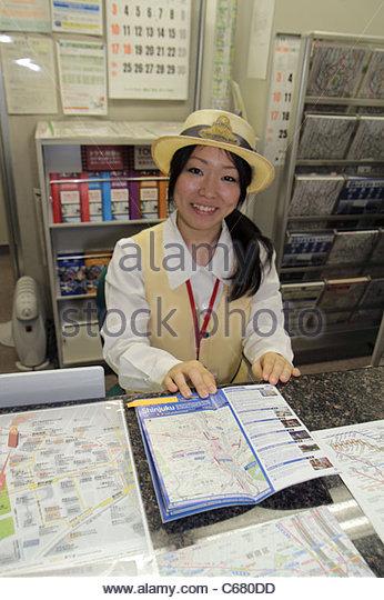 Tokyo Japan Shinjuku Shinjuku Station train subway information desk booth Asian woman help map uniform - Stock Image
