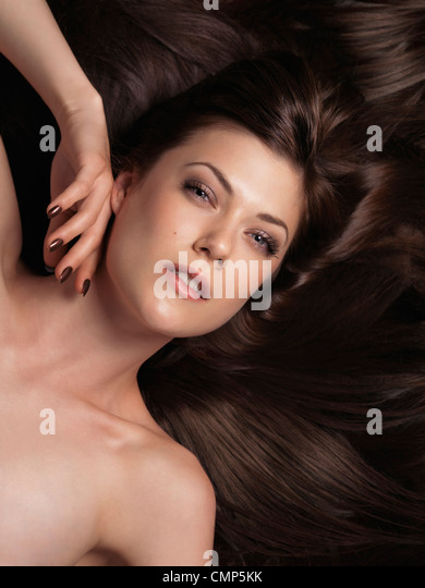 Beautiful young woman with long brown hair - Stock Image