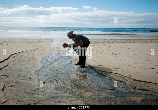Father and toddler looking at rippled sand at the beach - Stock Image