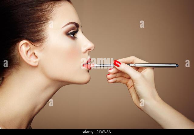 Makeup artist applies lipstick. Beautiful woman face. Perfect makeup - Stock Image