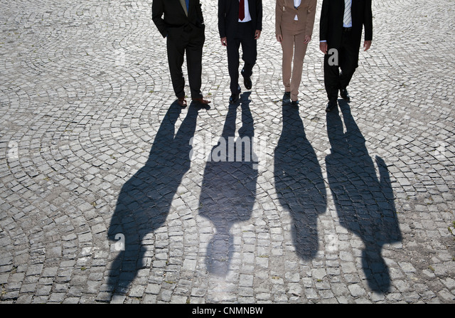 Shadows walking on cobbled road - Stock Image