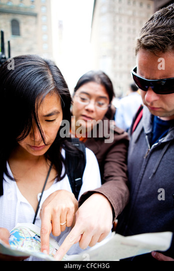 Friends look at a map on a walking tour in the city streets of Boston Massachusetts, MA. - Stock Image