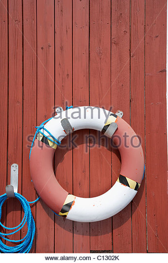 life buoy hanging on wall - Stock Image