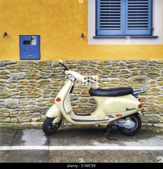 Vespa parked on the street - Stock Image