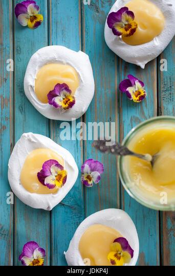 Mini pavlova with lemon curd and flowers - Stock Image