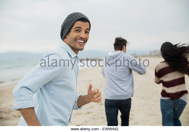 Portrait smiling man running with friends on beach - Stock-Bilder