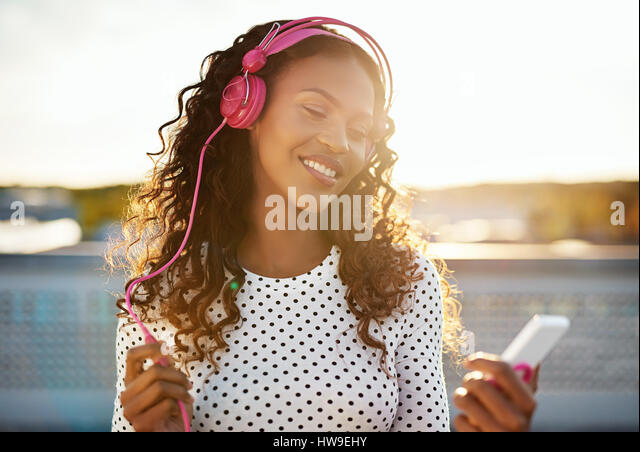 Portrait of a black lady enjoying the music on her phone - Stock Image