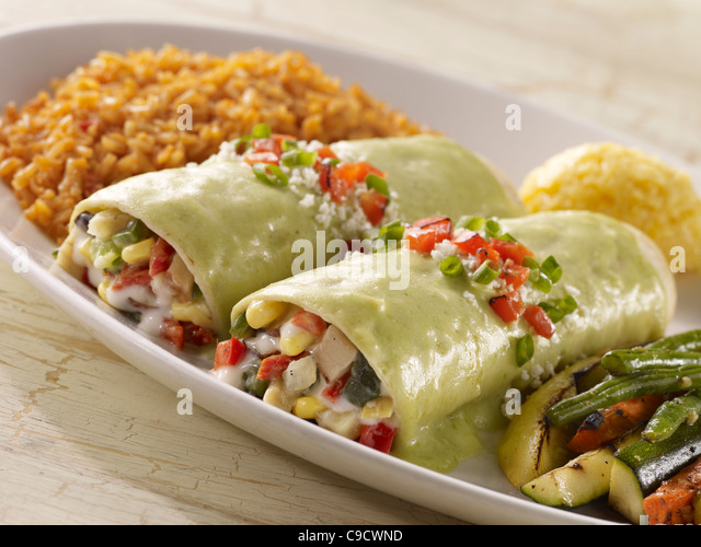 Two vegetable enchiladas topped with creamy green sauce and served with grilled vegetables and Spanish rice - Stock Image