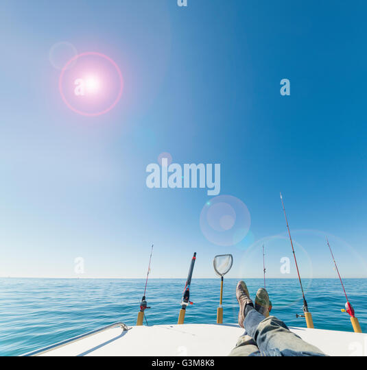 Fishing rods and mans legs on sailboat - Stock Image