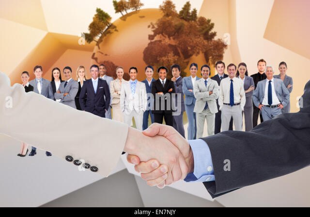 Composite image of smiling business people shaking hands while looking at the camera - Stock Image