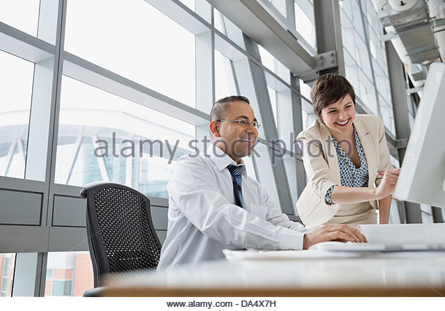 Businesswoman showing project on computer monitor in office building - Stock Image