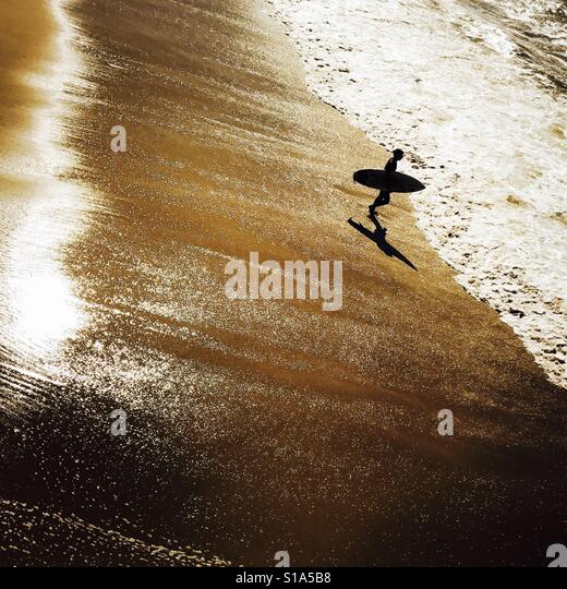 Surfer walking into the surf. Manhattan Beach, California USA. - Stock Image