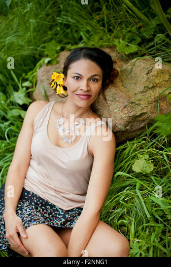Mixed race woman laying on rock in tall grass - Stock-Bilder