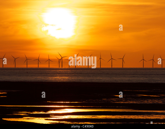 Wind farm with the sun setting in the background - Stock Image