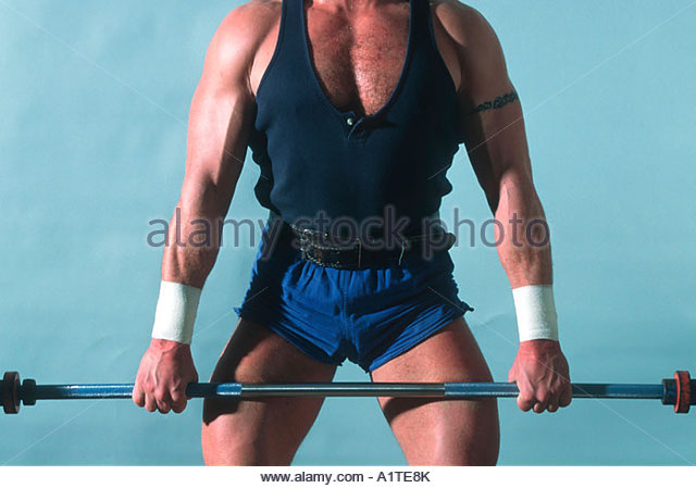 man weightlifting at fitness studio - Stock Image